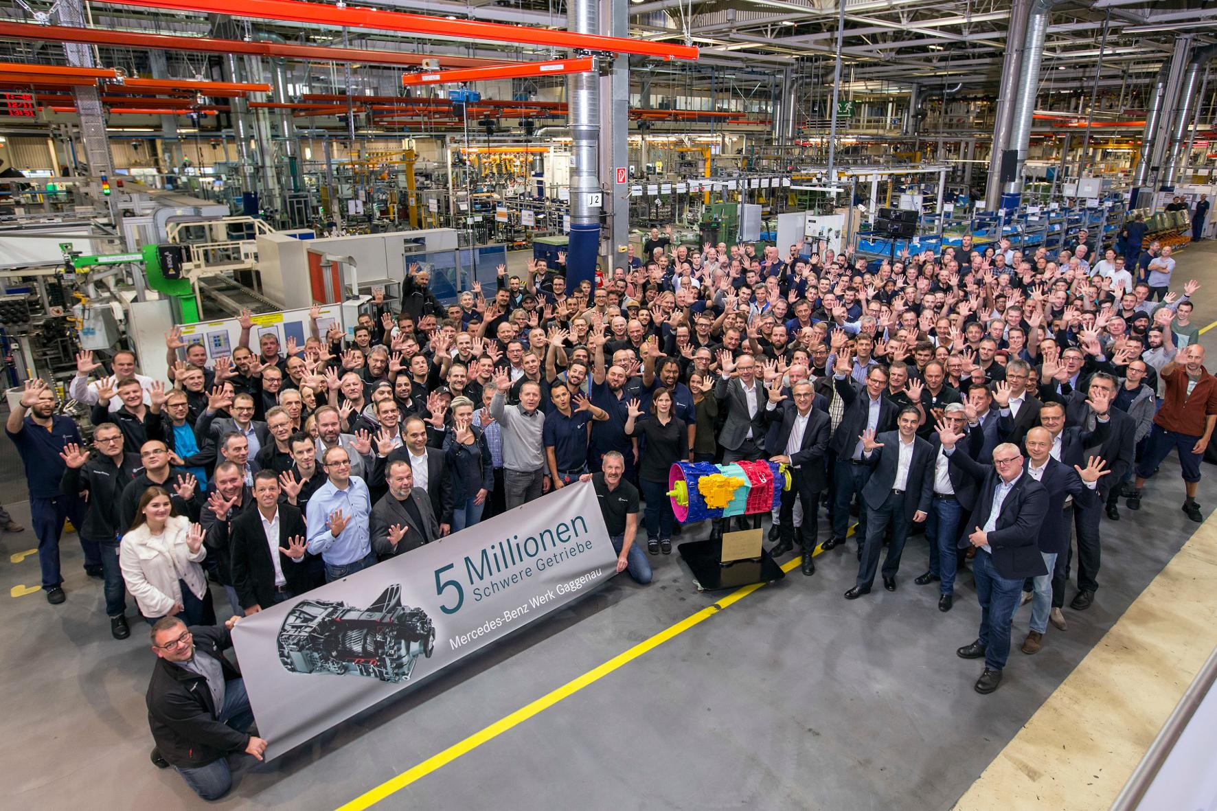 mid Groß-Gerau - Die stolze Mannschaft vor dem fünfmillionsten Getriebe, das anlässlich des Jubiläums bunt lackiert ist. Daimler